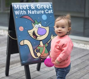 toddler in front of nature cat sign